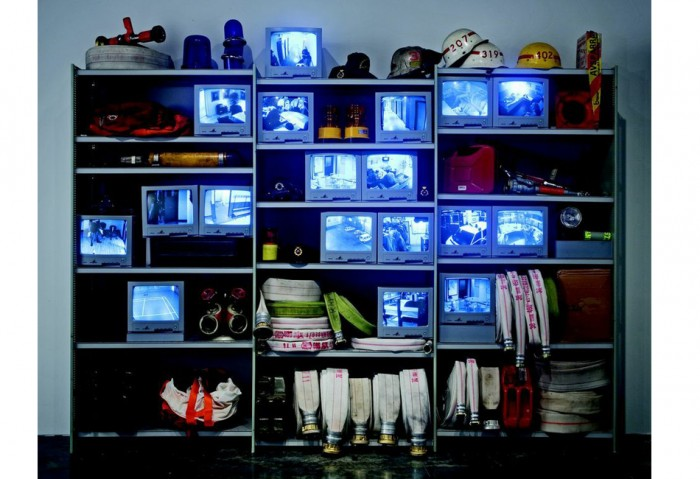 <i>Station 10 and Back Again</i>, 2001<br>DVD installation, 18 channels, black-and-white silent 18 surveillance monitors on metal shelves, 81 3/4 x 115 x 16 inches (207.65 x 292.1 x 40.64 cm)<br>Gift of the Martin Z. Margulies Foundation