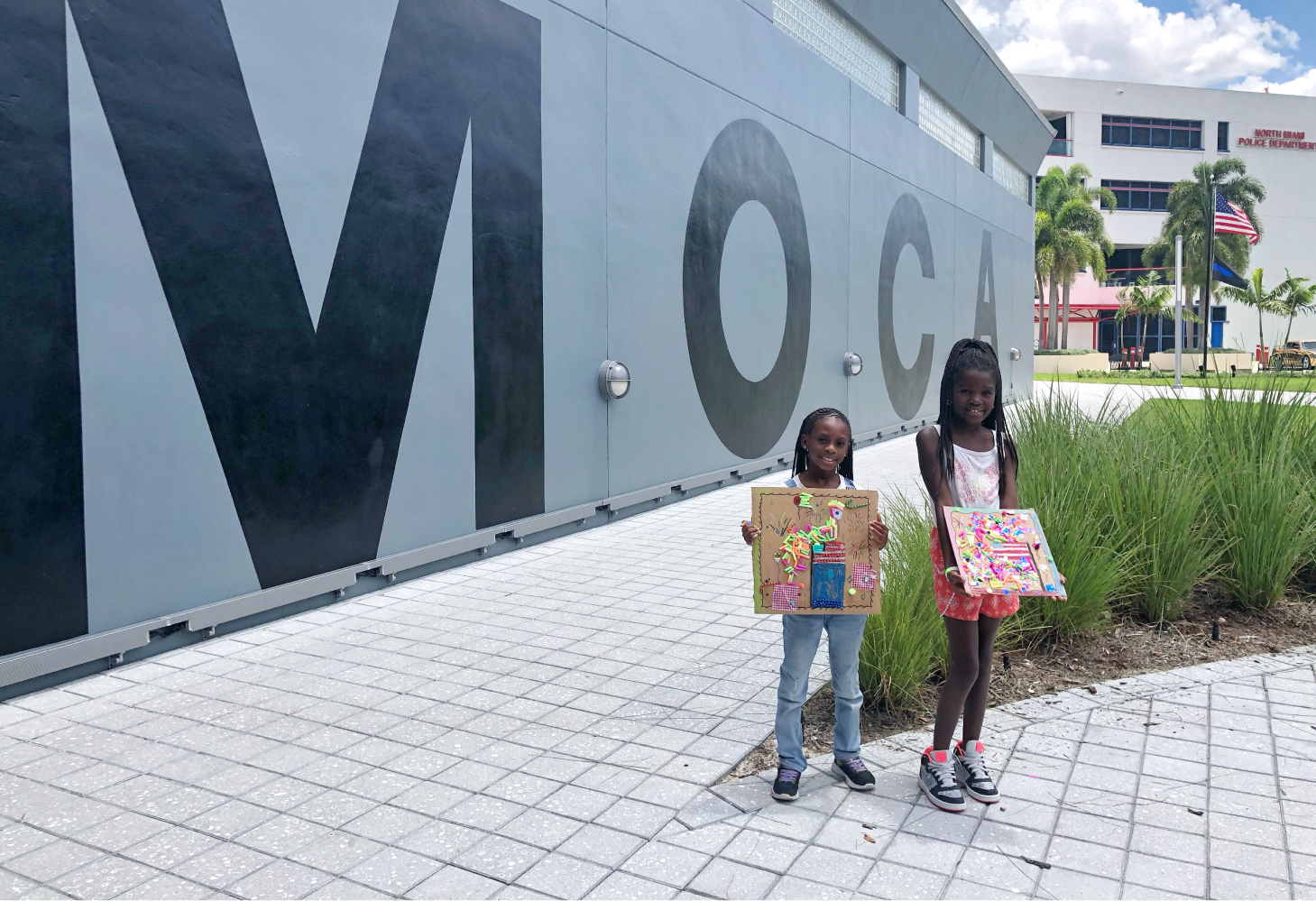 2 young Art Camp students hold their July 4th / Potoprens inspired creations in front of MOCA building