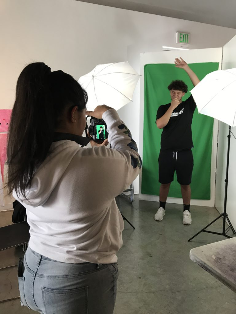 Teens taking photos in front of a green screen