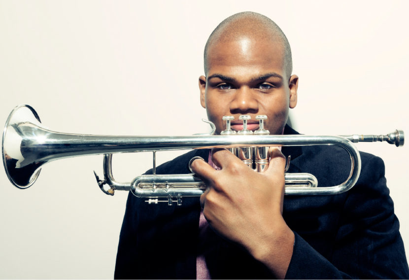 Curtis taylor holding a trumpet in front his face