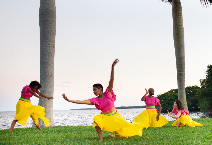 4 dancers in magenta tops and yellow skirts dance on grass besides water in various positions