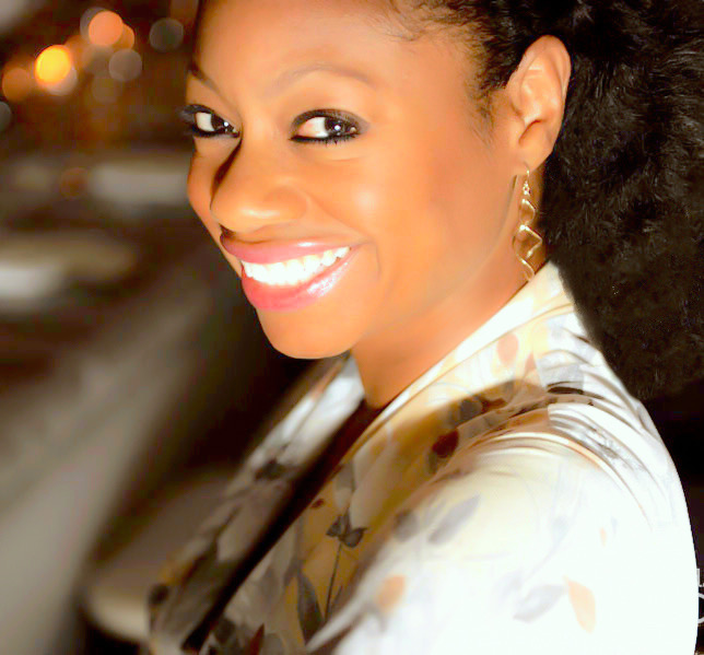 headshot of Donnamarie Baptiste taken at night with background light in bokeh